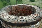 Blower of circular brick stack made by hollow radial bricks. Typically covered by concrete shield (relicts on the left).